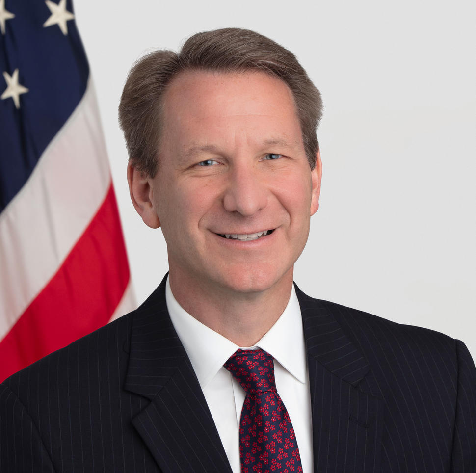 """NCI Director Norman """"Ned"""" Sharpless in front of an American flag"""